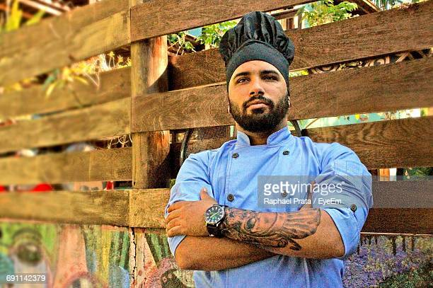 Chef With Arms Crossed Standing By Wooden Fence