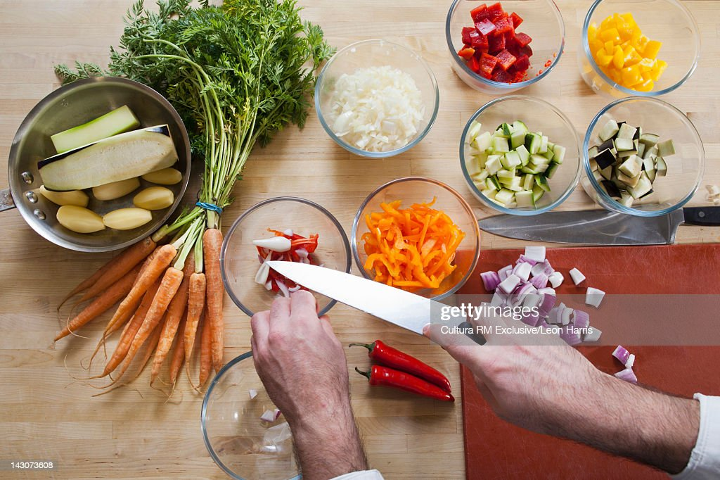 Chef with chopped vegetables in bowls