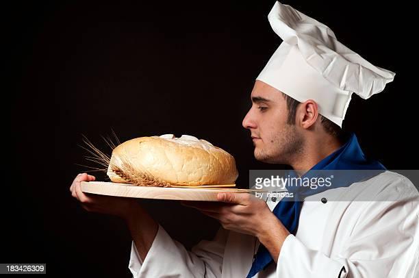 Küchenchef mit frischem Brot, isoliert auf Schwarz