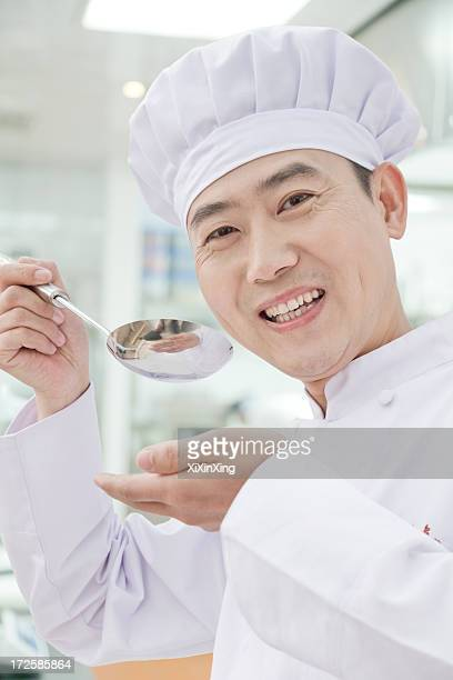 Chef with spoon, tasting food, portrait