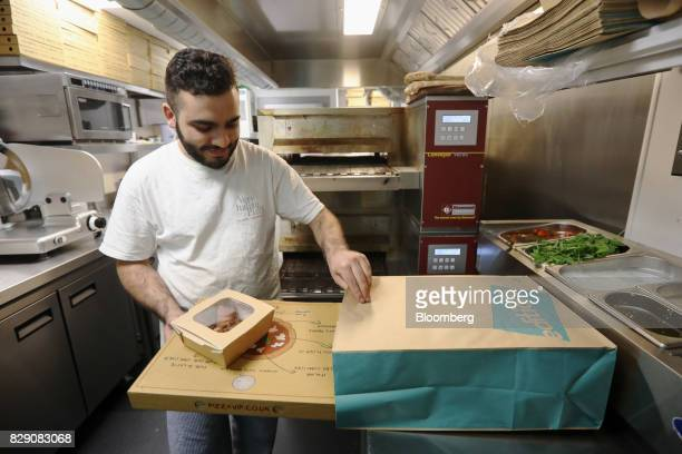 A chef with VIP Pizza deliveryonly kitchen places an order in a bag at a Deliveroo Editions field kitchen operated by Roofoods Ltd in Hove UK on...