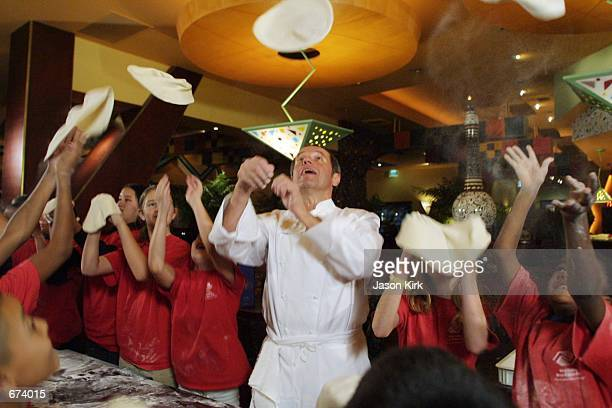 Chef Wolfgang Puck tosses a pizza up in the air as he teaches children from the West Valley Boys and Girls Club how to make pizza during a fundraiser...