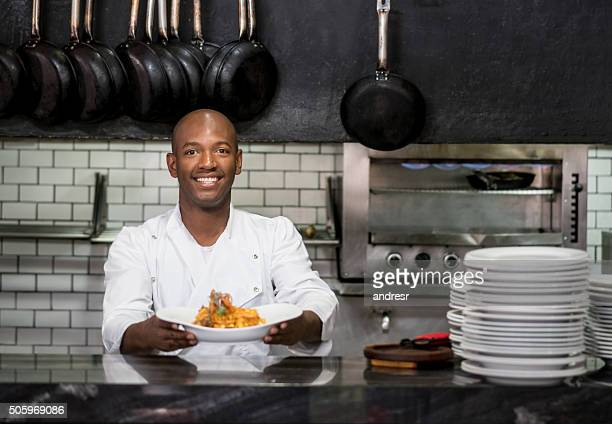 Chef working in a kitchen and showing his plate