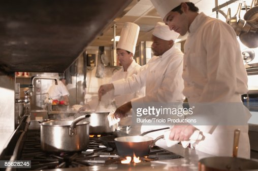 chefs cooking in restaurant kitchen stock photo getty images