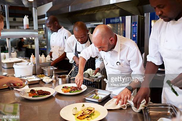 Chefs finishing dishes at kitchen, before serving