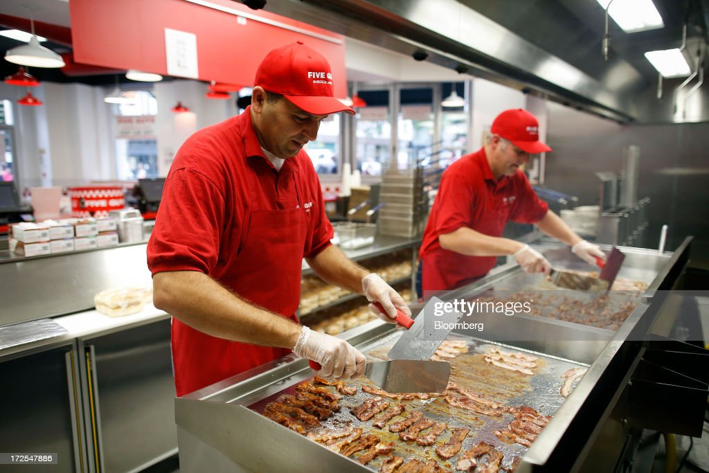 Chefs fry bacon on a griddle in the kitchen at U.S. burger restaurant chain Five Guys in London, U.K., on Tuesday, July 2, 2013. Five Guys, which is set to open its first U.K. store in Covent Garden on July 4, is a family outfit that started in Washington, D.C., in 1986, and has expanded to more than 1,000 locations in the U.S. and Canada. Photographer: Simon Dawson/Bloomberg via Getty Images