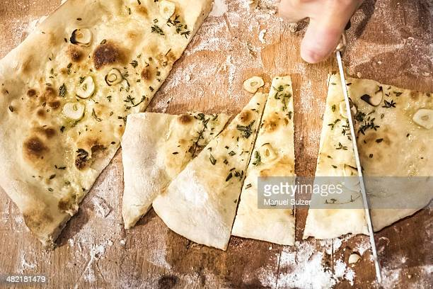 Chef's hand slicing pizza bread in commercial kitchen