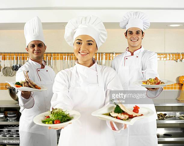 chefs holding plates of food