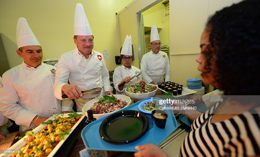 Chefs of world leaders serve dishes they prepared to New York residents in need, at Xavier Mission food pantry in New York, July 27, 2013. Chefs to President Obama, the Queen of England, President of France, King of Sweden, Chancellor of Germany, President of India, King of Thailand, Prince of Monaco, were among the 20 Chefs of World Leaders (Le Club des Chefs des Chefs or C.C.C.) preparing and serving dishes to New Yorkers in need as part of charity drive to help local food banks for poor people. (L-R) Chef to Monaco Prince Albert II Christian Garcia, Chef in charge of the official receptions of Switzerland, Gregor Zimmermann, Chef to US President Barack Obama, Cristeta Pasia Comeford and Chef to French president Francois Hollande Bernard Vaussion. AFP PHOTO/Emmanuel Dunand