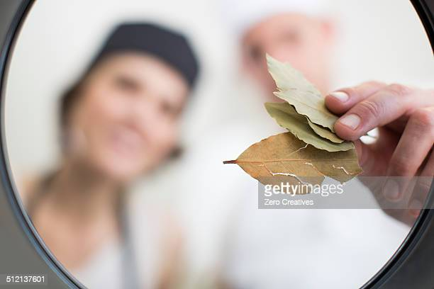 Chefs placing bay leaves into saucepan in commercial kitchen