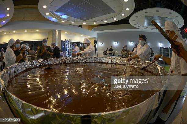 Chefs prepare chocolate while attempting to set a Guinness World Record for the largest chocolate coin in Caracas on October 1 2015 AFP PHOTO/JUAN...