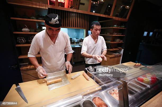 Chefs prepare sushi dishes in the kitchen of a Planeta Sushi restaurant operated by Rosinter Restaurants Holding OJSC in Moscow Russia on Thursday...