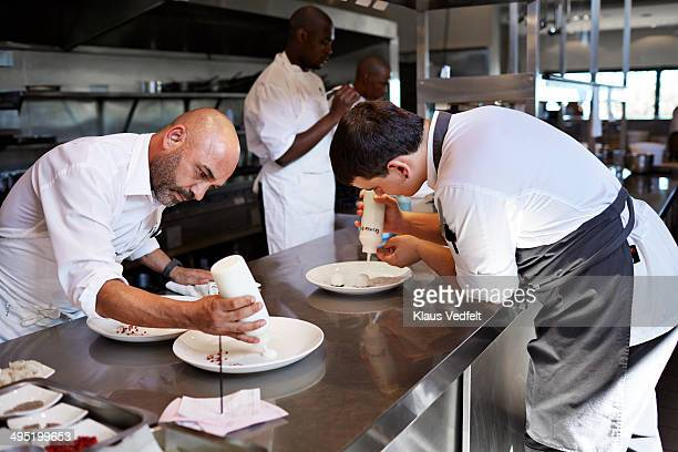 Chefs preparing food in kitchen at restaurant