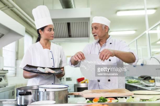 Chefs preparing spring rolls in restaurant