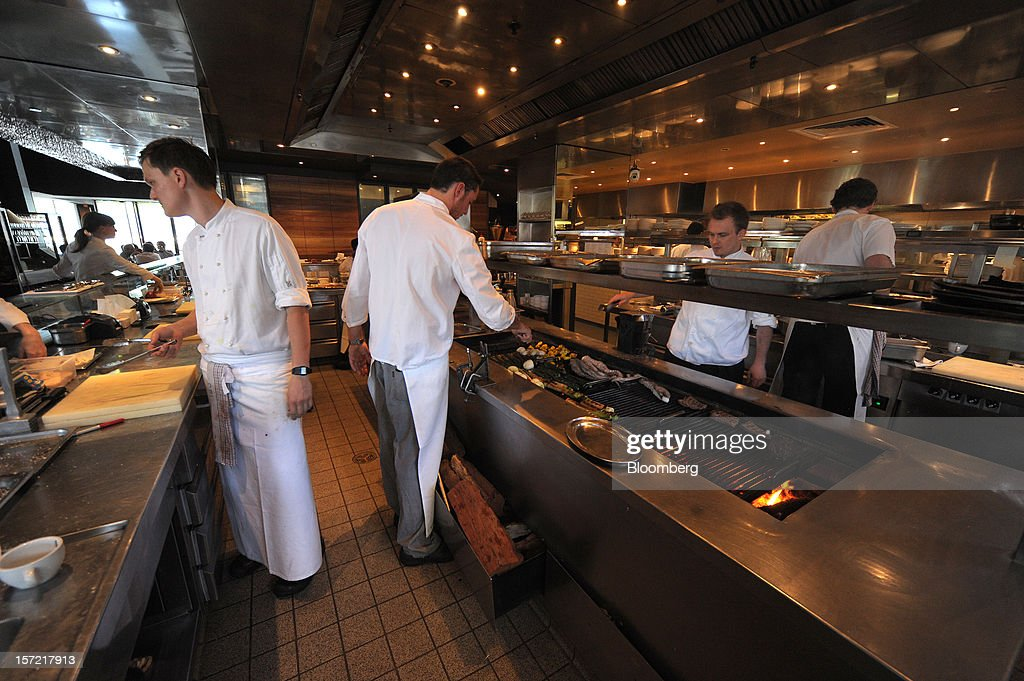 Chefs work around the grill in the kitchen at Rockpool Bar and Grill restaurant in Melbourne, Australia, on Wednesday, Nov. 28, 2012. The Australian Bureau of Statistics is expected to release November inflation data on Dec. 3. Photographer: Carla Gottgens/Bloomberg via Getty Images