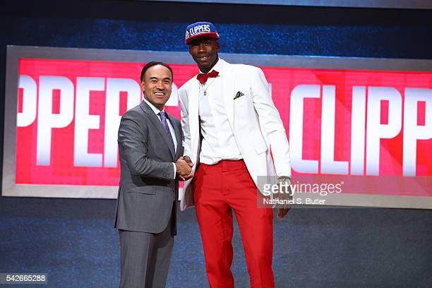 Cheick Diallo shakes hands with NBA Deputy Commissioner and Chief Operating Officer Mark Tatum after being selected number thirty third overall by...