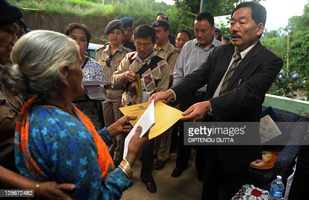 Cheif Minister of Indian state of Sikkim Pawan Chamling hands documents for relief grant applications to a villager from Nanduk on the outskirts of...