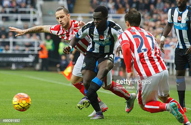 Cheik Ismael Tiote of Newcastle United competes for the ball against Marko Arnautovic and Bojan Krkic of Stoke City during the Barclays Premier...