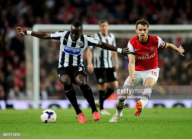 Cheik Ismael Tiote of Newcastle United holds off Aaron Ramsey of Arsenal during the Barclays Premier League match between Arsenal and Newcastle...