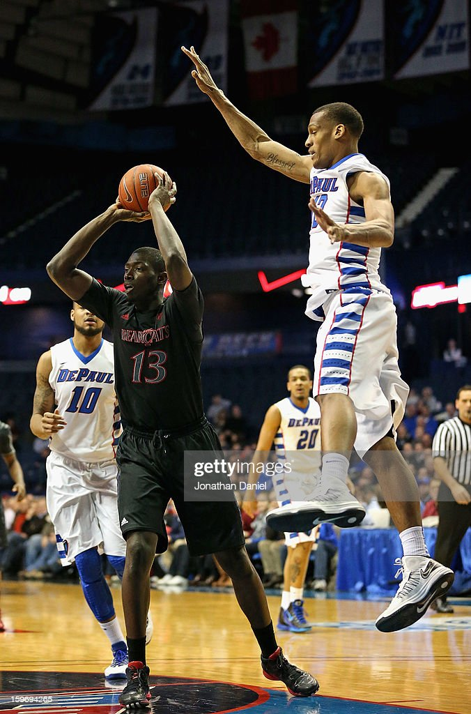 Cheikh Mbodj #13 of the Cincinnati Bearcats passes under pressure from Cleveland Melvin #12 of the DePaul Blue Demons at Allstate Arena on January 15, 2013 in Rosemont, Illinois. Cincinnati defeated DePaul 75-70.