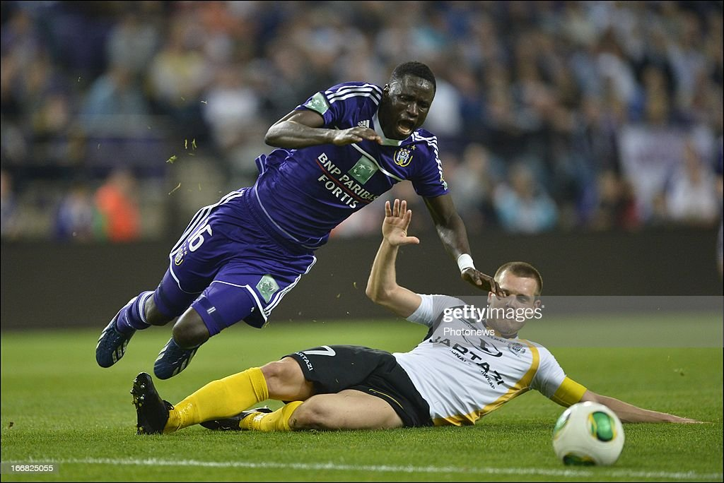 Cheikhou Kouyate of RSC Anderlecht is tackled by Killian Overmeire of Sporting Lokeren OVL during the Jupiler League play-off 1 match between RSC Anderlecht and Sporting Lokeren OVL on April 17, 2013 in the Constant Vanden Stock Stadium in Anderlecht, Belgium.