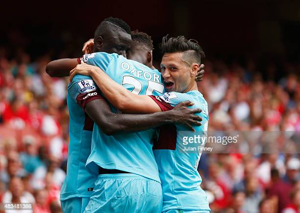 Cheikhou Kouyate of West Ham United celebrates scoring the opening goal with team mates during the Barclays Premier League match between Arsenal and...
