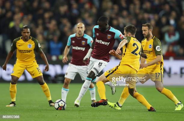 Cheikhou Kouyate of West Ham United holds off Davy Propper of Brighton and Hove Albion during the Premier League match between West Ham United and...
