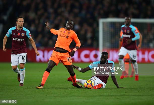 Cheikhou Kouyate of West Ham United tackles Sadio Mane of Liverpool during the Premier League match between West Ham United and Liverpool at London...