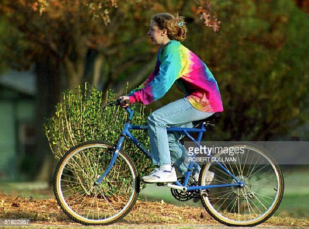 Chelsea Clinton daughter of US President elect Bill Clinton rides a bicycle 14 November on the grounds of the Governor's mansion The Clintons will...