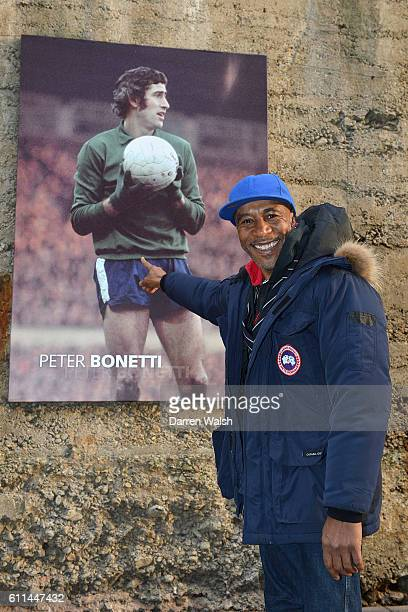 Chelsea fan Danny JohnJules poses for a photo outside the ground before the game
