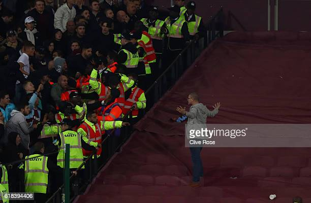 Chelsea fan gets past the police line and walks over to West Ham United fans during the EFL Cup fourth round match between West Ham United and...