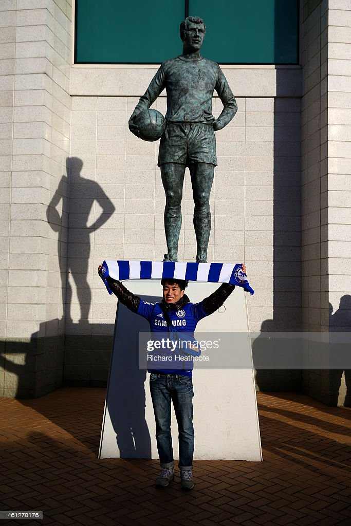 A Chelsea fan poses next to the Peter Osgood statue outside the stadium before the Barclays Premier League match between Chelsea and Newcastle United at Stamford Bridge on January 10, 2015 in London, England.