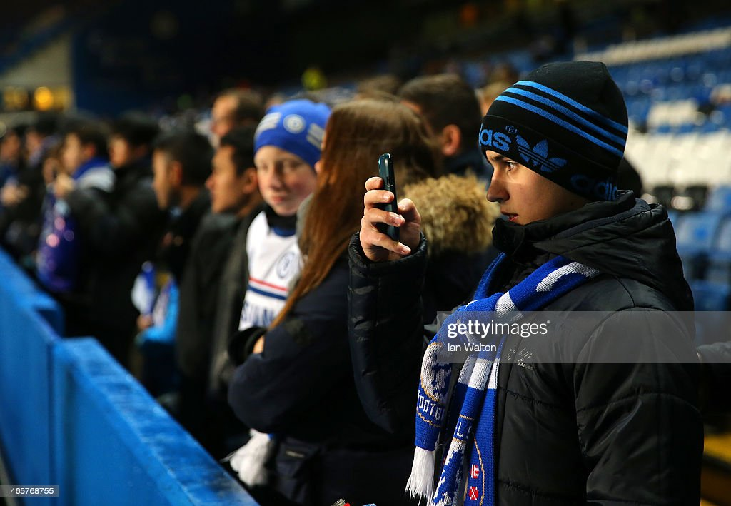 A Chelsea fan take a photo on his smart phone ahead of the Barclays Premier League match between Chelsea and West Ham United at Stamford Bridge on January 29, 2014 in London, England.