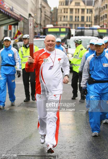 Chelsea football club CEO Peter Kenyon carries the Olympic torch during its relay journey across London on its way to the lighting of the Olympic...