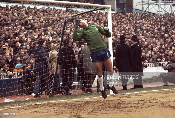 Chelsea Football Club player Peter Bonetti midjump at the goalpost during a football match