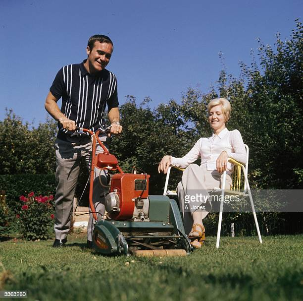 Chelsea footballer Ron Harris mows the lawn as his wife watches him from a garden chair
