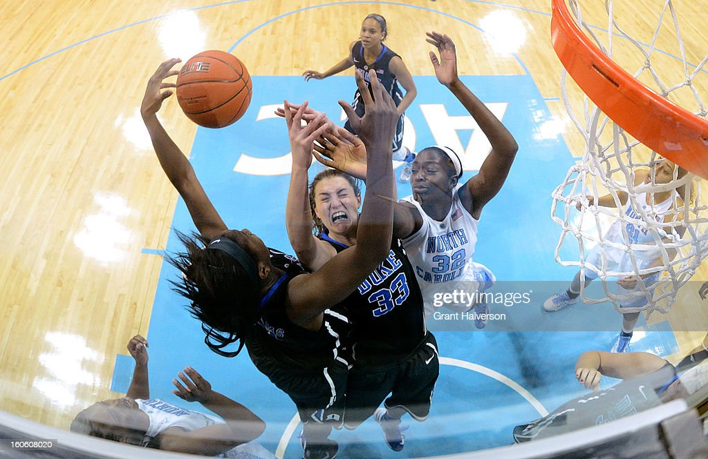 Chelsea Gray #12 and Haley Peters #33 of the Duke Blue Devils battle for a rebound with Waltiea Rolle #32 of the North Carolina Tar Heels during play at Carmichael Arena on February 3, 2013 in Chapel Hill, North Carolina. Duke won 84-63.