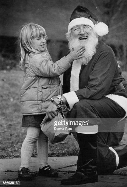 Chelsea Kline touches Santa's beard to see if its real It is Santa is father Declan Madden Priest from St Francis Inert faith center Credit Denver...