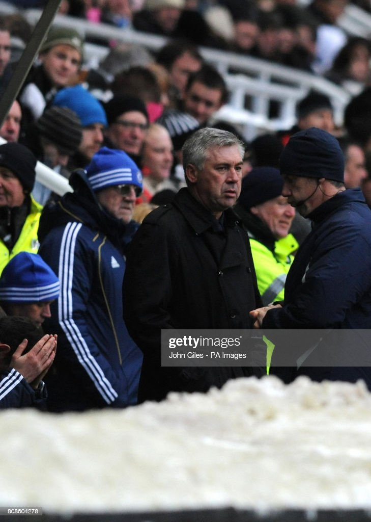 Chelsea manager Carlo Ancelotti stands behind piles of snow as he watches during the Barclays Premier League match at St James' Park, Newcastle.