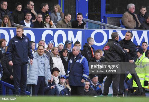Chelsea manager Jose Mourinho is restrained by the fourth offcial as Everton manager David Moyes turns away
