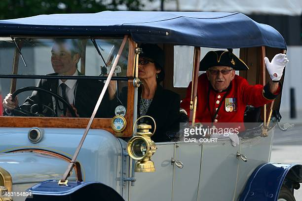 A Chelsea Pensioner a British war veteren from the Chelsea Royal Hospital waves from a car of World War 1 vintage as it drives through central London...
