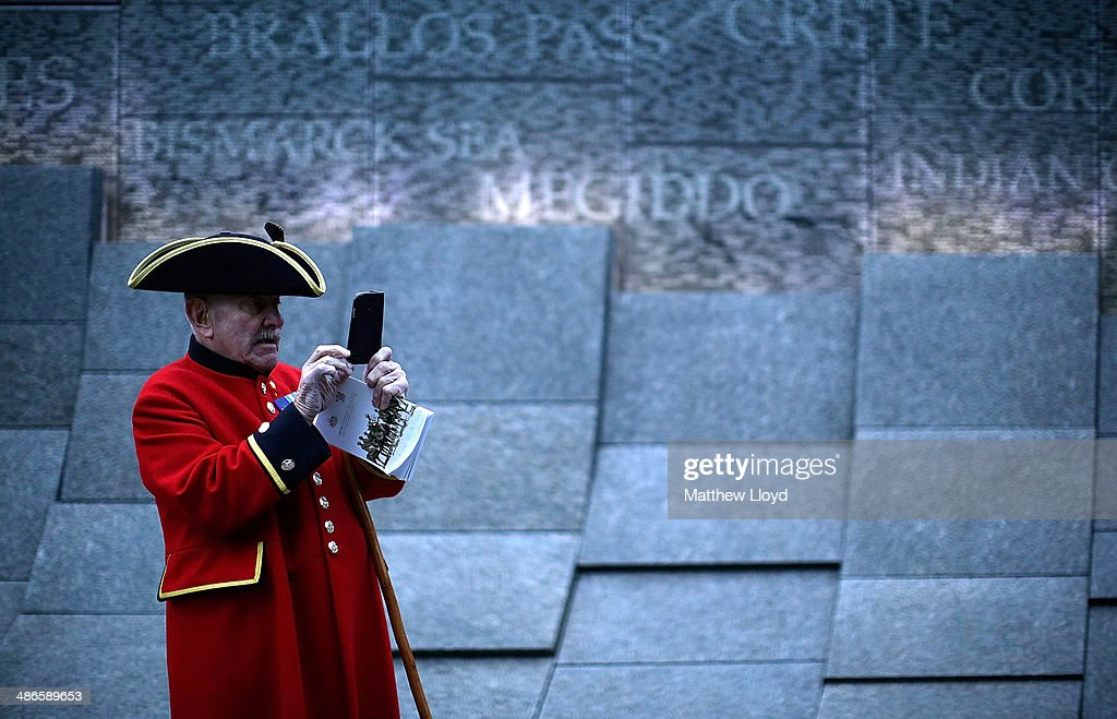 A Chelsea pensioner takes a picture on a mobile phone in front of the Australian War Memorial during a dawn remembrance service at the Wellington Arch on ANZAC Day at Hyde Park on April 25, 2014 in London, England. It is the 99th anniversary of the Galipoli landings in which tens of thousands of servicemen died.