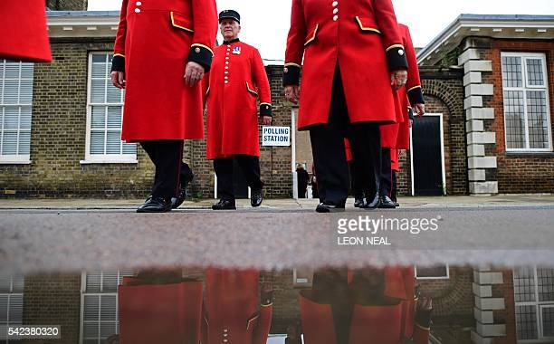 Chelsea pensioners are reflected in a puddle of rain water as they leave after being ushered into a polling station to cast their ballot papers at...