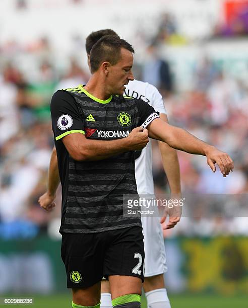 Chelsea player John Terry adjusts his captain's arm band during the Premier League match between Swansea City and Chelsea at Liberty Stadium on...