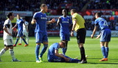 Chelsea players speak to referee Phil Dowd before Swansea City's Spanish defender Chico Flores is sent off for a tackle on Chelsea's German striker...