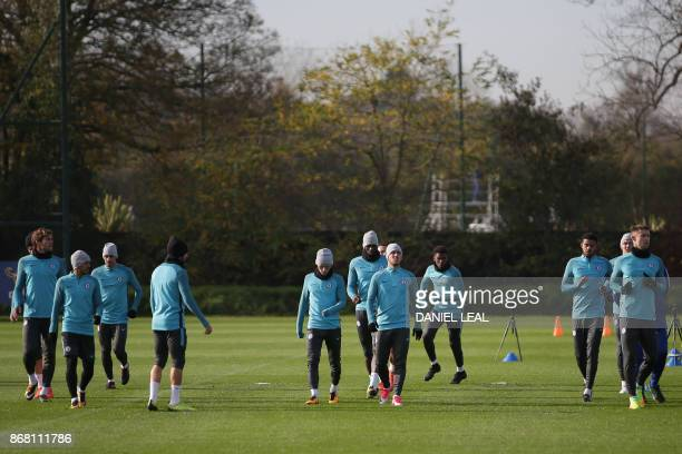 Chelsea players warm up at a training session at Chelsea's Cobham training facility in Stoke D'Abernon southwest of London on the eve of their UEFA...