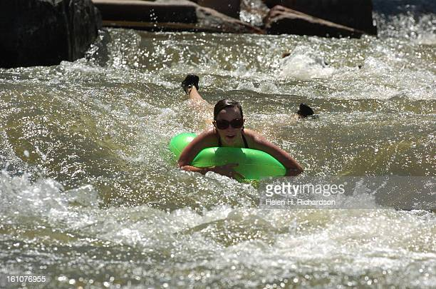 Chelsea Schaul <cq> of Phoenix Arizona has some fun riding the rapids on her small inner tube in Confluence Park She was joined by 3 of her college...