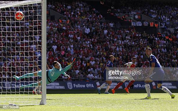 Chelsea's Belgian goalkeeper Thibaut Courtois cannot stop the shot from Arsenal's English midfielder Alex OxladeChamberlain giving Arsenal the lead...