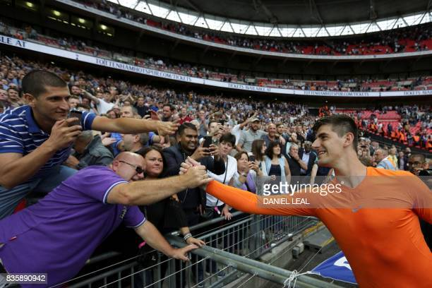 Chelsea's Belgian goalkeeper Thibaut Courtois celebrates victory with supporters after the English Premier League football match between Tottenham...