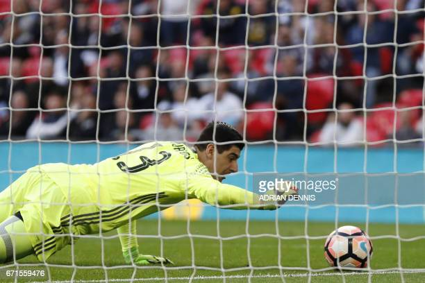 Chelsea's Belgian goalkeeper Thibaut Courtois saves a goal off Tottenham Hotspur's English striker Harry Kane's free kick during the FA Cup semifinal...